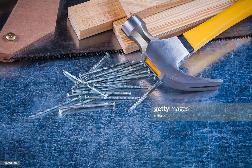 Close-up image of metal nails hammer wooden bricks hacksaw : Stock Photo