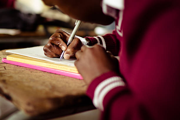 closeup image of south african girl writing at her desk picture