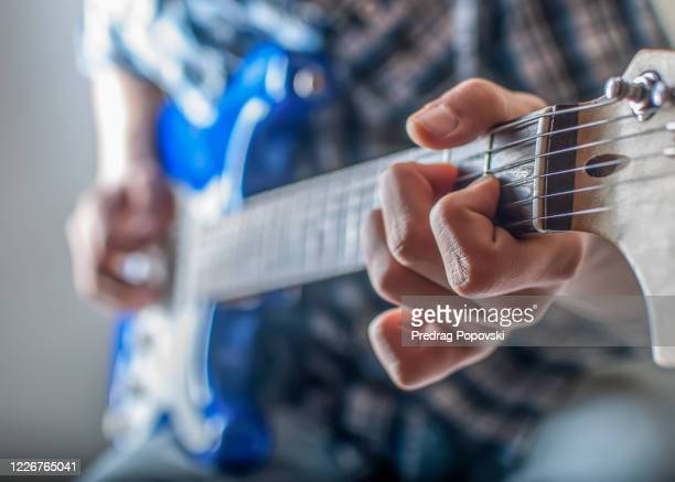 closeup image of young man playing on blue electric guitar - エレキギター ストックフォトと画像