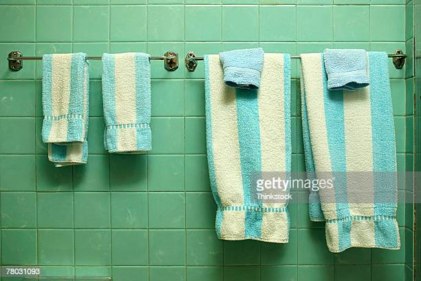 Close-up in a 1950s style bathroom of blue and white striped towels hanging against a green tiled wall.