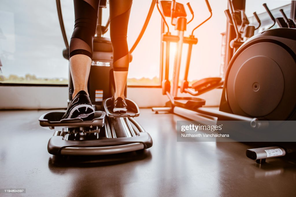 Closeup leg of cardio workout on an elliptical.people working out on an elliptical trainer in gym.Back view : Stock Photo