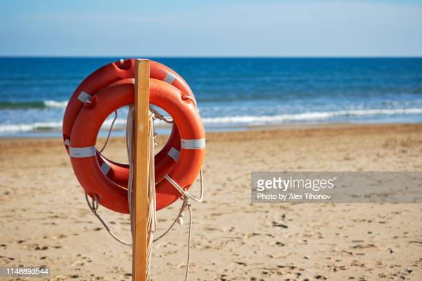 close-up lifebuoys on spanish beach - lifeguard stock pictures, royalty-free photos & images