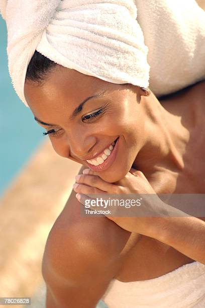 Close-up looking down on a smiling woman with towels wrapped around her hair and body and her hand on her shoulder.