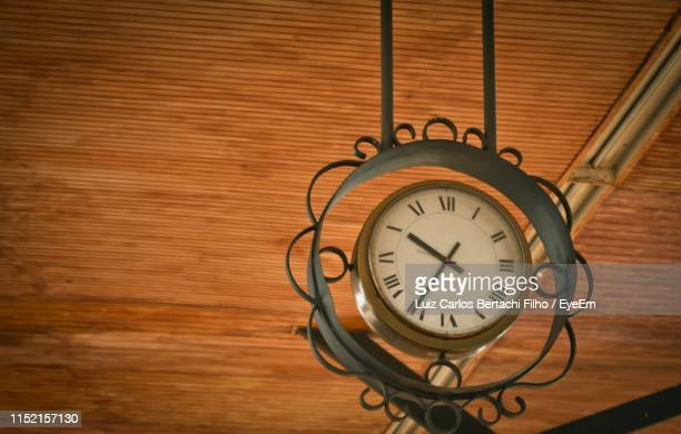 close-up low angle view of clock hanging from ceiling - filho stockfoto's en -beelden