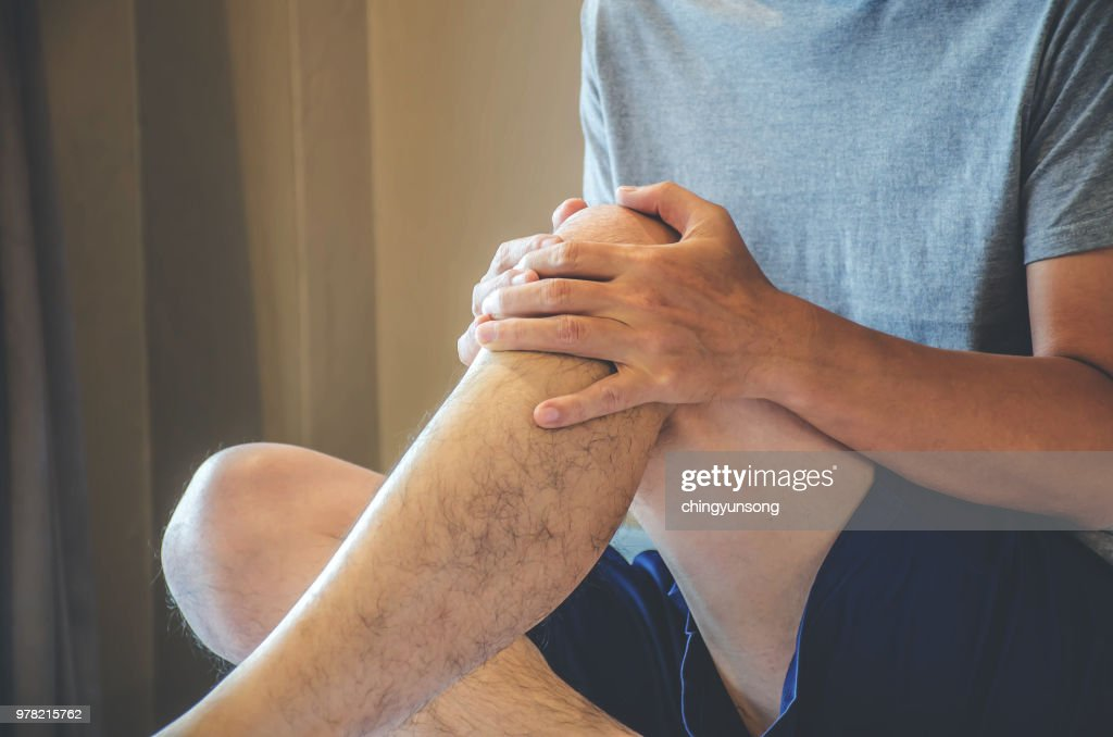 Closeup man hand holding knee with pain on bed, health care and medical concept : Stock Photo