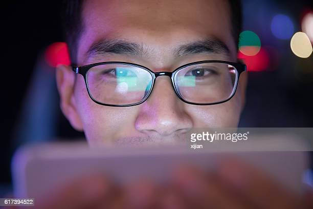 close-up man using mobile phone at night - projection screen stock pictures, royalty-free photos & images