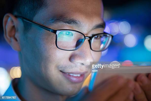 close-up man using mobile phone at night