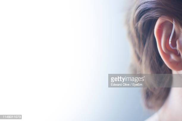 close-up man wearing hearing aid against wall - assistive technology stock pictures, royalty-free photos & images