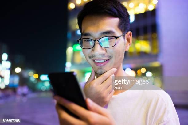 Close-up man with smart phone at night