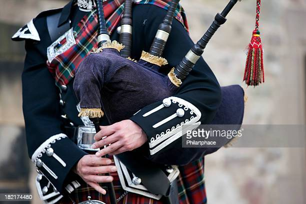 close-up mid section of a man playing the scottish bagpipes - kilt stock photos and pictures