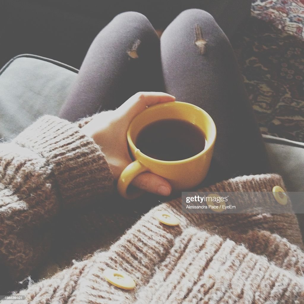 Close-up mid section of hand holding coffee cup on lap : Stock Photo
