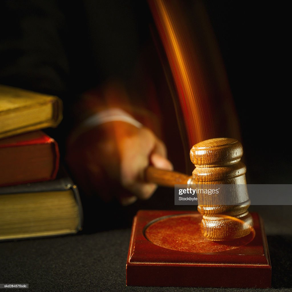 Close-up mid section of judge hitting gavel on pad : Stock Photo