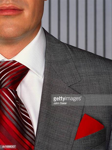 close-up mid section portrait of a well dressed businessman with a red handkerchief in his suit pocket - solapa fotografías e imágenes de stock