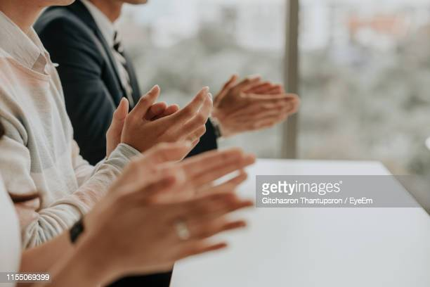 close-up midsection of business colleagues clapping in office - aplaudir fotografías e imágenes de stock