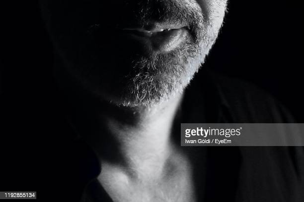 close-up midsection of man against black background - human mouth stock pictures, royalty-free photos & images