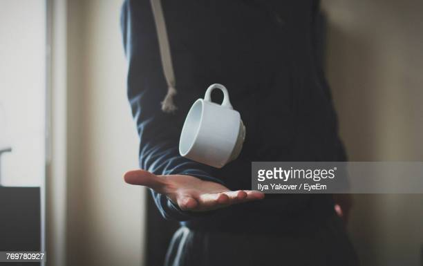 close-up midsection of man catching cup at home - catching stock pictures, royalty-free photos & images