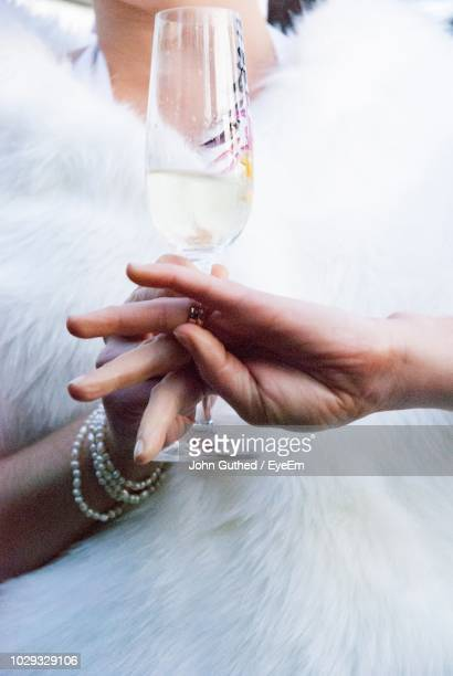 Close-Up Midsection Of Woman Holding Champagne Flute By Cropped Hand