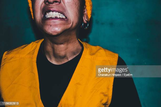 close-up midsection of young man clenching teeth at home - clenching teeth stock pictures, royalty-free photos & images