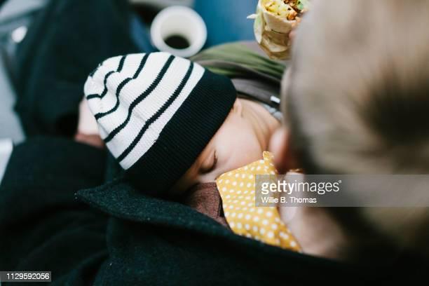 close-up mother holding her sleeping baby - nah stock-fotos und bilder
