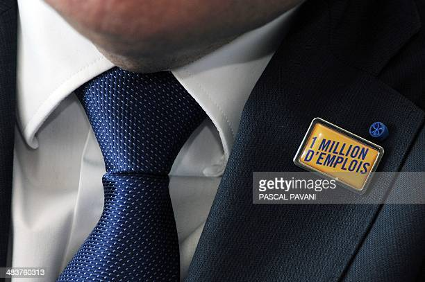 Closeup n the badge of French employers association Medef's head Pierre Gattaz which reads '1 million jobs' as aimed by Medef during a debate of the...