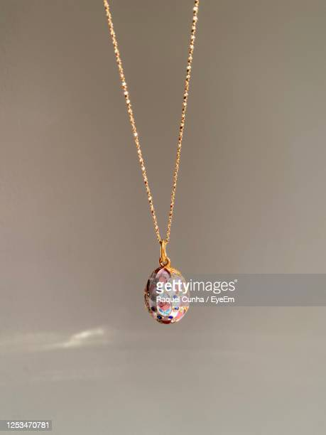 close-up necklace hanging against gray background - pendant stock pictures, royalty-free photos & images