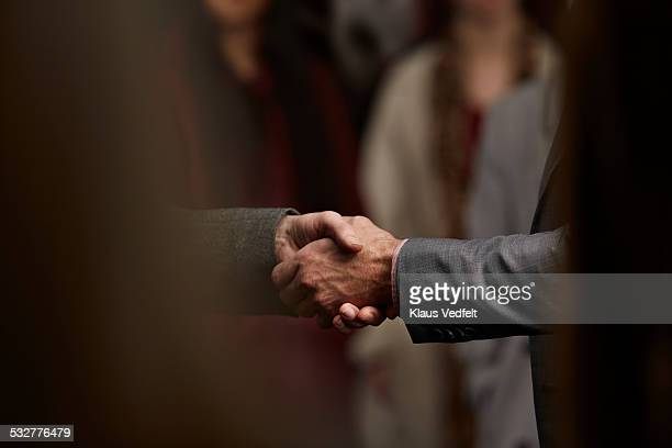 close-up of 2 men making handshake in crowd - handshake stock pictures, royalty-free photos & images
