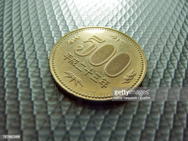 Close-Up Of 500 Yen Coin On Metallic Table