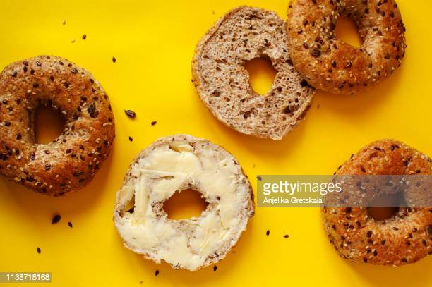 closeup of a 12 grain bagel with butter - bagels stock pictures, royalty-free photos & images