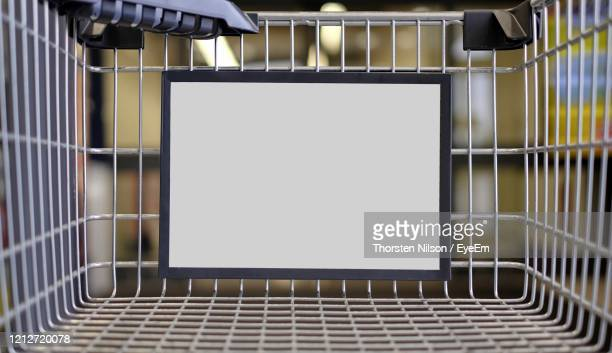 closeup of a advertising sign in a shopping cart. horizontal image with copy space. - shopping trolley stock pictures, royalty-free photos & images