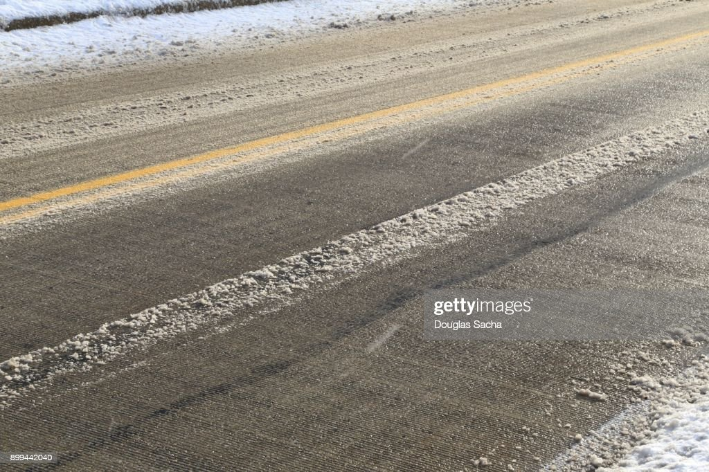 Close-up of a asphalt paved roadway covered with slushy snow : Stock Photo