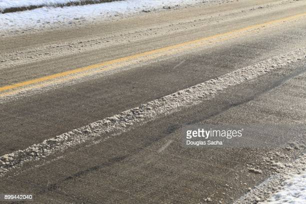 close-up of a asphalt paved roadway covered with slushy snow - sleet stock photos and pictures