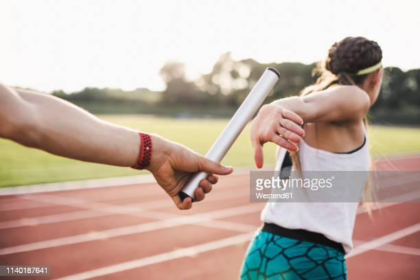 close-up of a athlete passing the baton to a female athlete - 団体競技 ストックフォトと画像