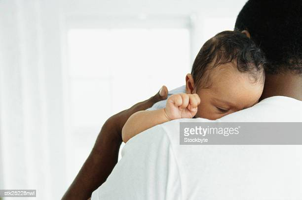 close-up of a baby asleep on father's shoulder