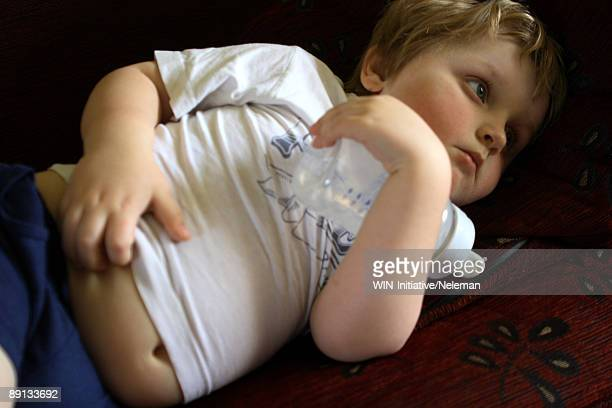 Close-up of a baby boy lying on the bed with a baby bottle, Republic of Ireland