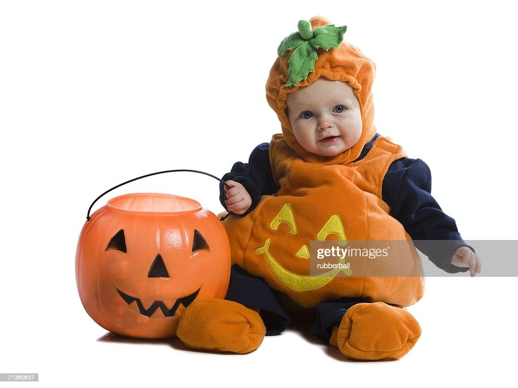 closeup of a baby girl in halloween costume and sitting on the floor