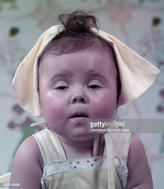 Closeup of a baby wearing yellow bonnet and yellow sun dress with eyes closed New York City USA