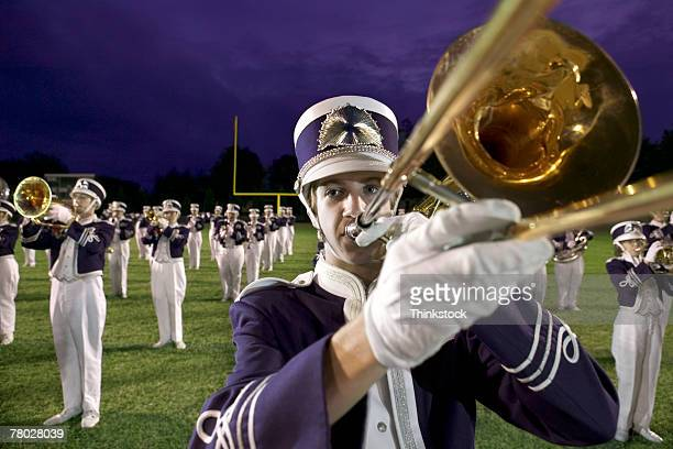 Close-up of a band member playing his trombone with the marching band performing in the background.