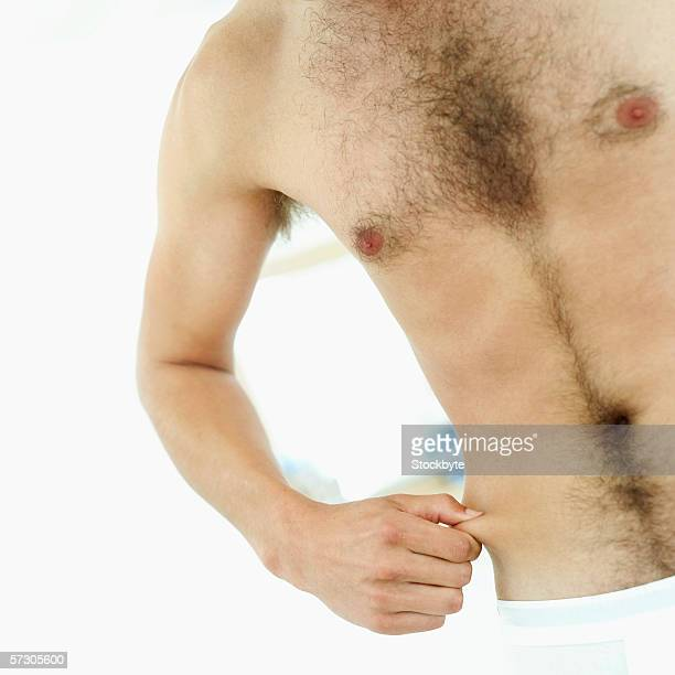 close-up of a bare-chested young man pinching his waist - bare chested man foto e immagini stock