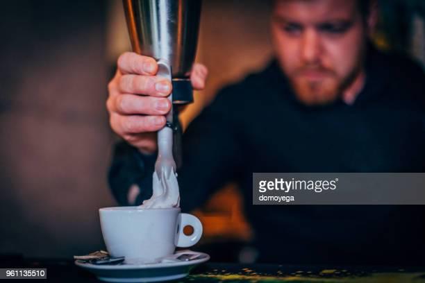 バーでコーヒーを作るバーテンダーのクローズ アップ カウンター