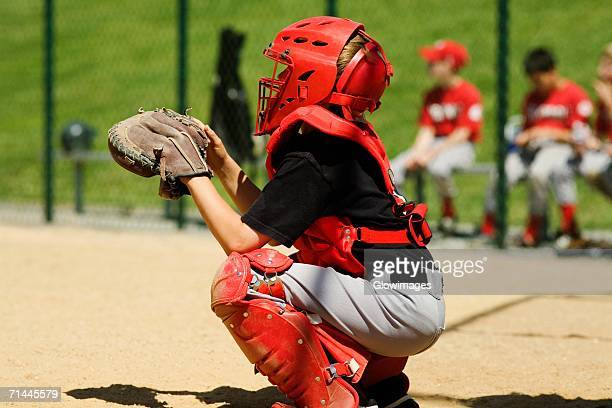 close-up of a baseball catcher crouching on a baseball field - caneleira roupa desportiva de proteção imagens e fotografias de stock