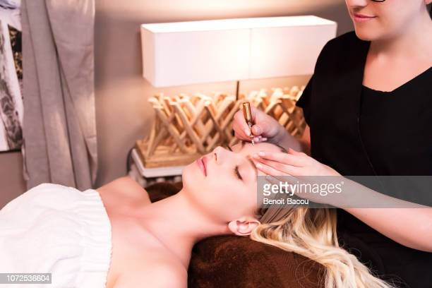 closeup of a beautician applying a skin care serum ampoule on a pretty woman. - beauty care occupation stock photos and pictures