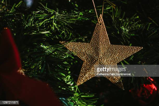 close-up of a beautiful gold christmas star hanging on a christmas tree - symbolism stock pictures, royalty-free photos & images