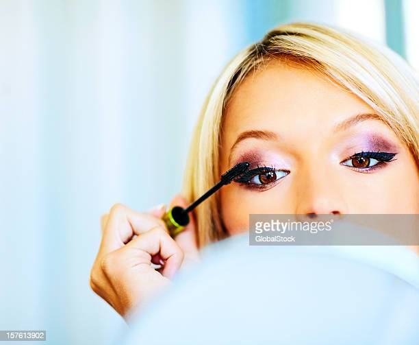 Close-up of a beautiful woman applying mascara