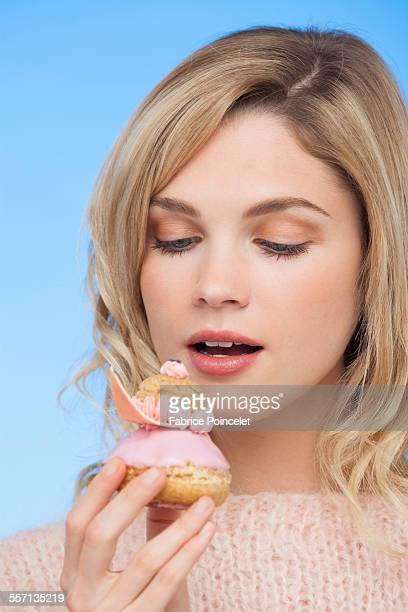 Close-up of a beautiful woman eating a french strawberry religieuse