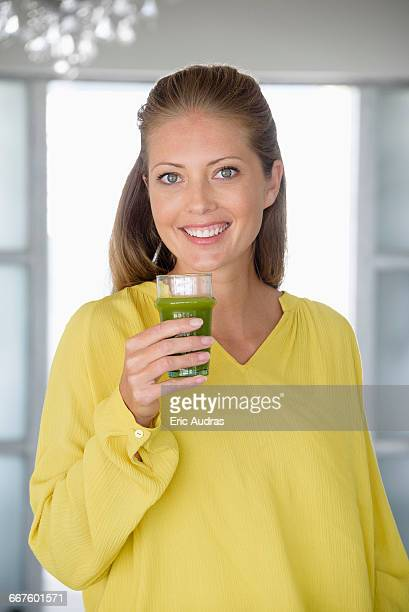 Close-up of a beautiful woman holding a glass of vegetable juice