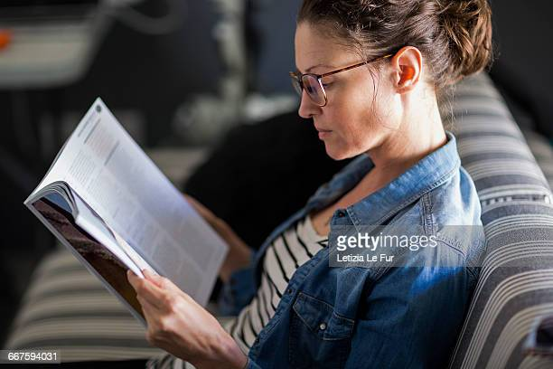 close-up of a beautiful woman reading a magazine - magazine stock pictures, royalty-free photos & images
