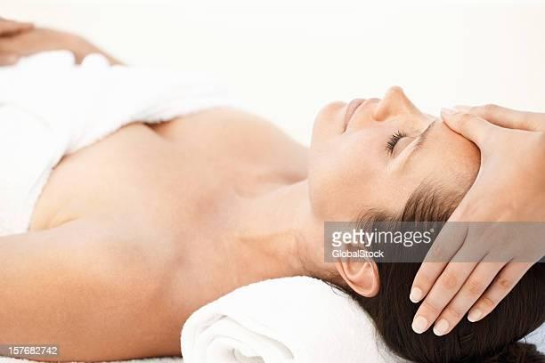 Closeup of a beautiful woman receiving head massage on white
