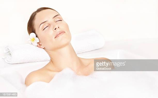 Close-up of a beautiful woman relaxing in bath tub