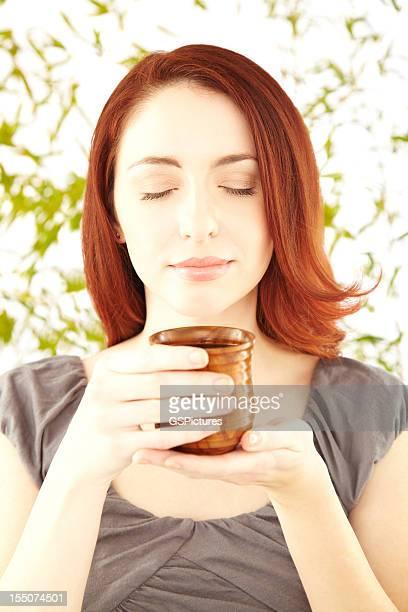 Primer plano de una mujer bella oliendo de té caliente
