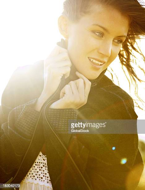 Closeup of a beautiful woman wrapped in jacket looks away